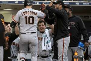 San Francisco Giants' Evan Longoria (10) is welcomed at the dugout after hitting a two-run home run during the fourth inning of a baseball game against the San Diego Padres in San Diego, Saturday, April, 14, 2018. (AP Photo/Kyusung Gong)