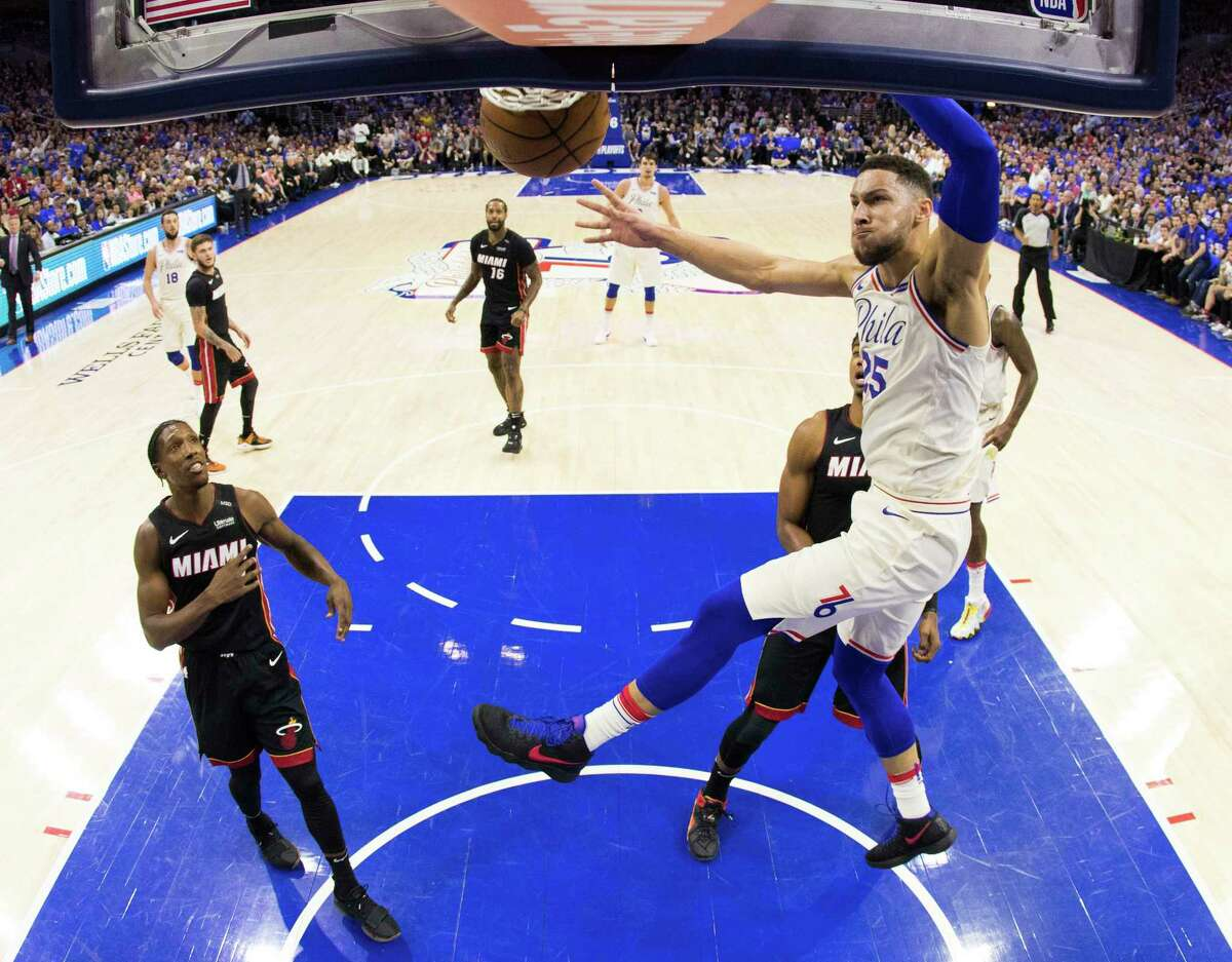 In this photo taken with a fisheye lens, Philadelphia 76ers' Ben Simmons, right, of Australia, dunks during the first half in Game 1 of a first-round NBA basketball playoff series against the Miami Heat, Saturday, April 14, 2018, in Philadelphia. (AP Photo/Chris Szagola)
