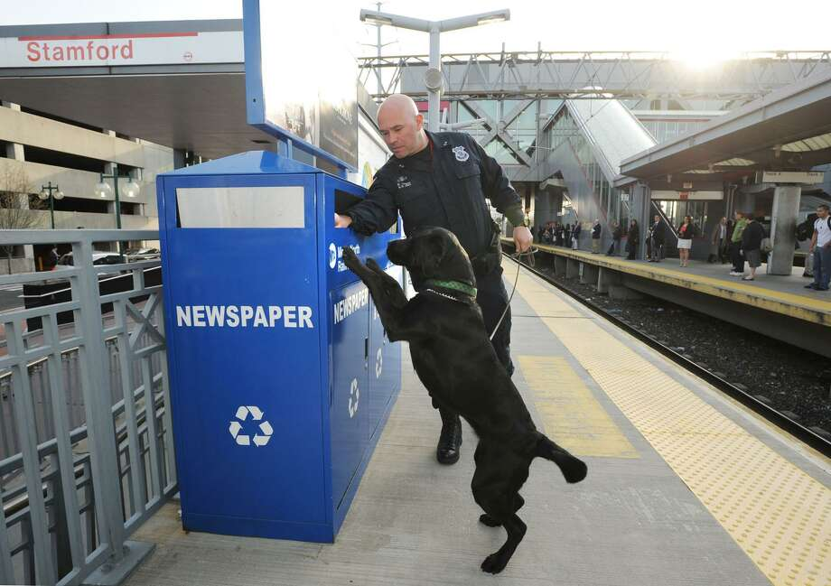 Stamford Police Officer Erin Trew and his black Labrador retriever, Riley, inspect a newspaper recycling receptacle at the Stamford Train Station on April 16, 2013. The Boston Marathon bombing the day before had put the nation's police forces on high alert. Photo: Bob Luckey / File Photo / Greenwich Time