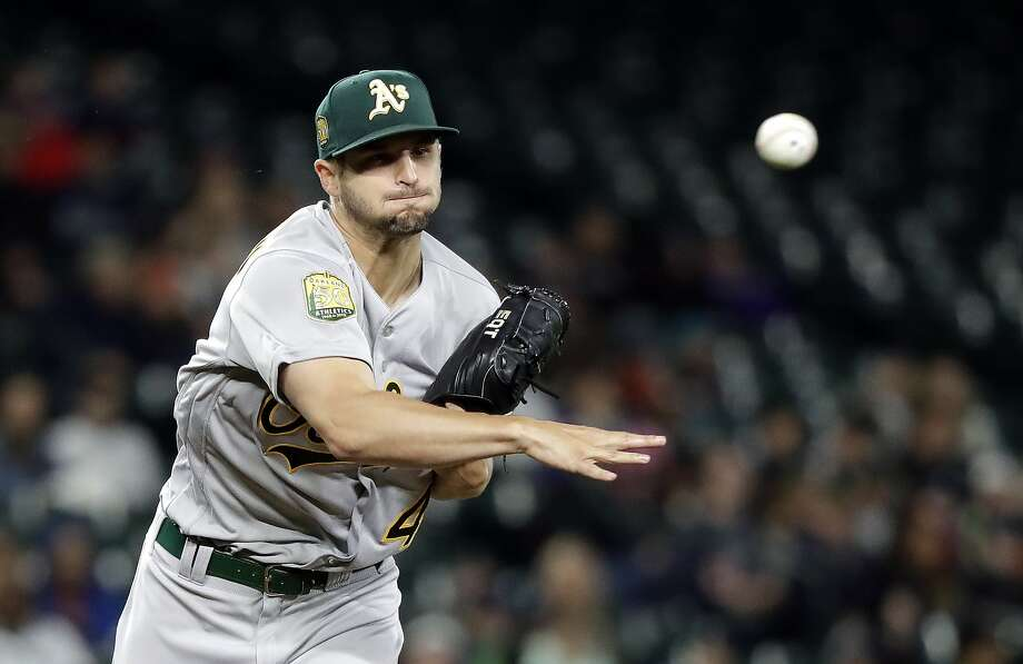 Oakland Athletics starting pitcher Kendall Graveman throws to first base on a pickoff-attempt of Seattle Mariners' Dee Gordon in the first inning during a baseball game Saturday, April 14, 2018, in Seattle. Gordon was safe on the play. (AP Photo/Elaine Thompson) Photo: Elaine Thompson / Associated Press