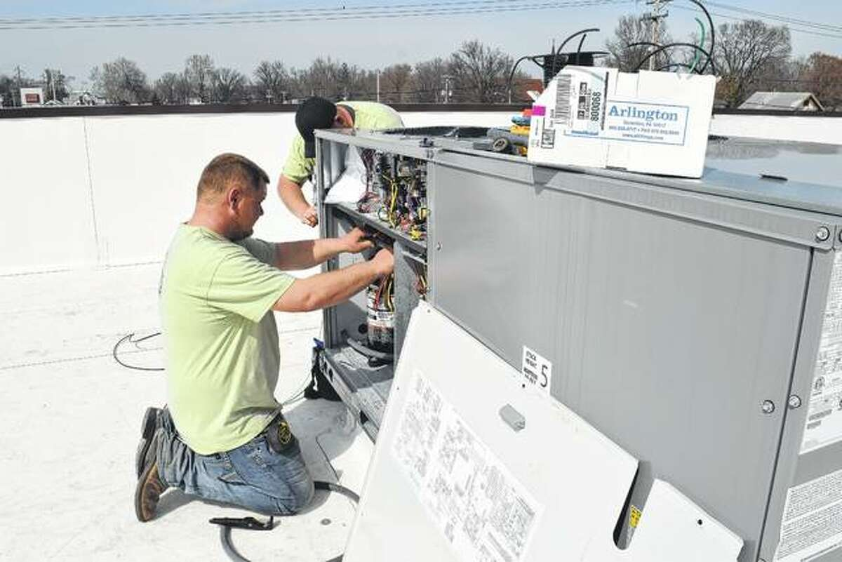 Harley McQuinn of Edinburg (left) and Michael Dauphinee of Springfield, employees of Jim Watts Electric of Springfield, work Thursday on wiring an air conditioner on the roof of the Dunkin' Donuts shop that is scheduled to open in June at South Main Street and East Morton Avenue.