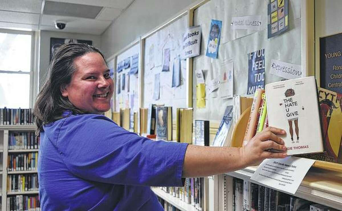 """Jacksonville Public Library children's librarian Cindy Boehlke shelves """"The Hate U Give,"""" a book on the American Library Assoication's challenged-books list."""