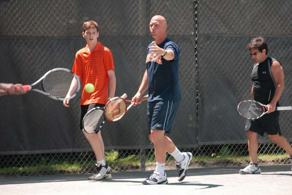 Tennis player Luke Jensen gives hitting tips to tennis student Zack Fashouer during one of his clinics at the Colonie Country Club. (Kayla Galway / Times Union)