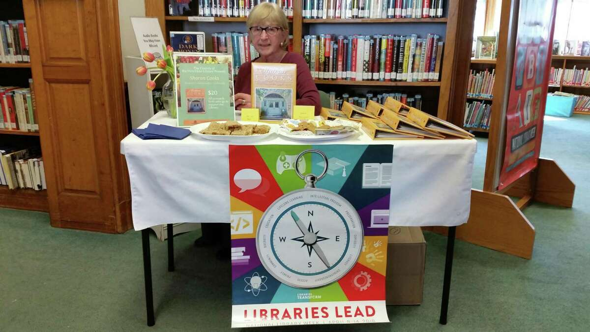 """Library Board of Directors member Linda Peech works the baked-goods table derived from recipes of the cookbook on sale, ?""""Sharon Cooks!,?"""" the Library's 2017 community cookbook."""
