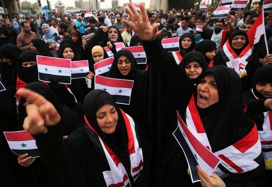 Iraqis wave Syrian flags during a protest in Baghdad against the U.S.-led air strikes on Syria. The U.S., Britain and France hit sites they said were linked to a chemical weapons program. Photo: Ahmad Al-Rubaye / AFP / Getty Images