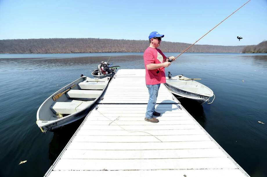Geoffrey Scales of Cobalt, Connecticut, fishes off of a floating dock at Lake Saltonstall in Branford. Photo: Arnold Gold / Hearst Connecticut Media / New Haven Register