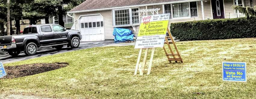 Signs urging residents to vote 'no' on the sewer referendum in Burnt Hills on Sunday.
