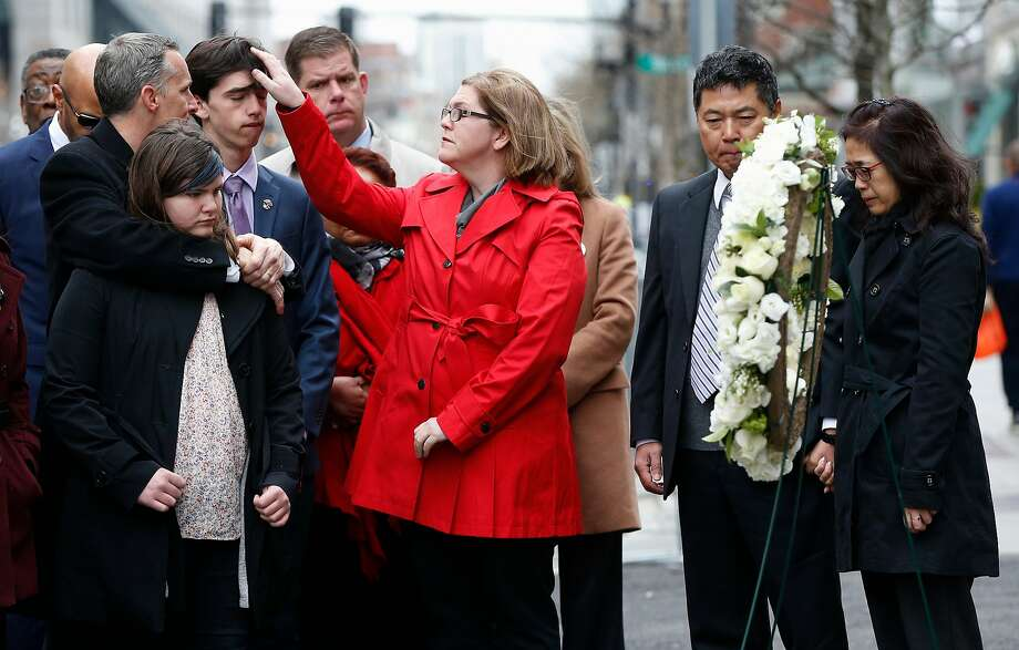 The family of Martin Richard — foreground from left: Bill, Jane, Henry and Denise — observe a moment of silence with The father of Lingzi Lu, Jun Lu (second from right) and her aunt Helen Zhao (right) during a ceremony at the site where Martin Richard and Lingzi Lu were killed in the second explosion at the 2013 Boston Marathon. Photo: Michael Dwyer / Associated Press