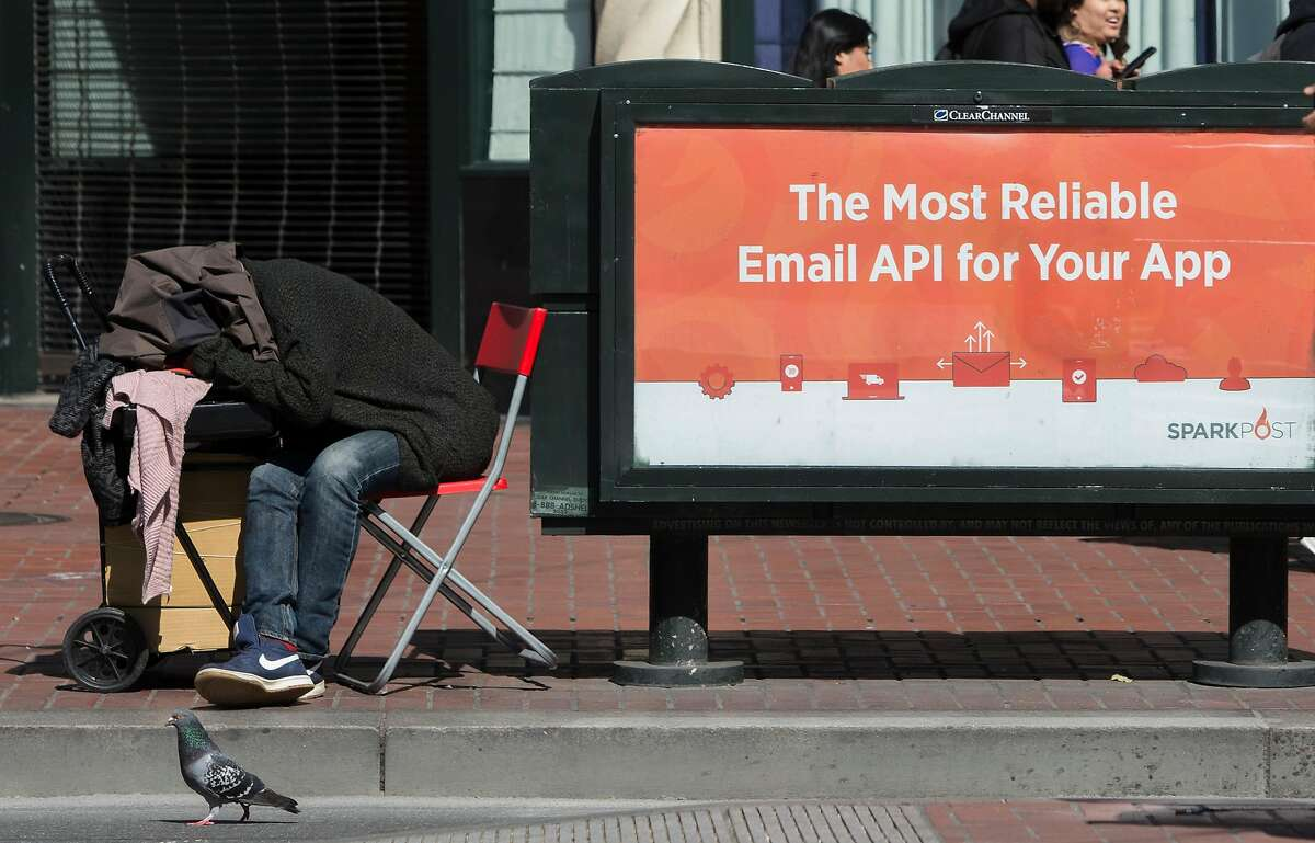 A homeless man sleeps on a chair next to a tech app advertisement on Market Street Friday, April 13, 2018 in San Francisco, Calif.