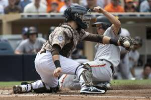 San Diego Padres catcher Austin Hedges, left, cannot catch the throw at home plate as San Francisco Giants' Nick Hundley, right, slides in to score during the second inning of a baseball game in San Diego, Sunday, April, 15, 2018. (AP Photo/Kyusung Gong)