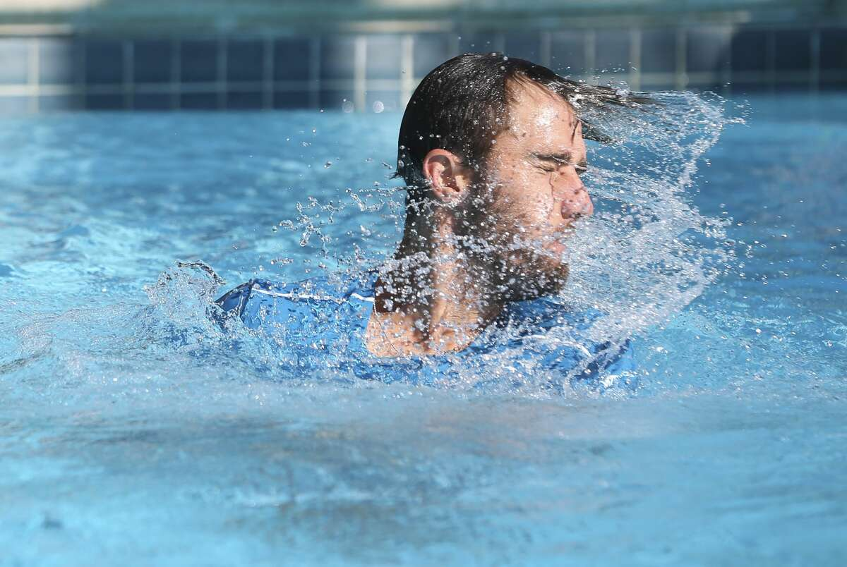 Steve Johnson dives into the pool after winning the U.S. Men?'s Clay Court Championship title, a tradition, at River Oaks Country Club on Sunday, April 15, 2018, in Houston. Johnson defeated Tennys Sandgren, both of United States, for his second title back-to-back 7-6, 2-6 and 6-4. ( Yi-Chin Lee / Houston Chronicle )