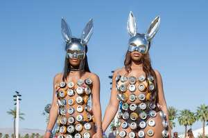 "Chanel Twyman (L), 23, and Auzuanay Watkins, 25, both of Philadelphia, Pennsylvania pose at the Coachella Music and Arts Festival in Indio, California, April 14, 2018. Coachella became one of the world's premier music festivals not only for the A-list performers. The two-weekend party in the California desert has become a major event in its own right for the fashion. While designers have heavily marketed their brands to Coachella, the fans who draw the most notice often do so by embracing their own sartorial flair, driven by a sense of innovation and, among revelers in the searing heat, of inhibition.  / AFP PHOTO / Kyle Grillot / TO GO WITH AFP STORY by Shaun TANDON, ""From flowers to bondage, a fashion bonanza at Coachella""KYLE GRILLOT/AFP/Getty Images"