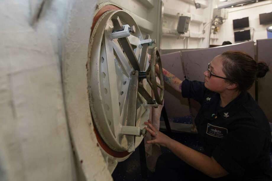170419-N-BY095-0063  PACIFIC OCEAN  Information Systems Technician 2nd Class Kacee Jensen, from Catskill, N.Y., conducts maintenance on a scuttle aboard the Arleigh Burke-class guided-missile destroyer USS Shoup (DDG 86) while underway for a composite training unit exercise (COMPTUEX) with the Nimitz Carrier Strike Group in preparation for an upcoming deployment. COMPTUEX tests the mission readiness of the strike group's assets through simulated real-world scenarios and their ability to perform as an integrated unit. (U.S. Navy photo by Mass Communication Specialist 3rd Class Maria I. Alvarez/Released) Photo: Seaman Maria Alvarez / Public Domain