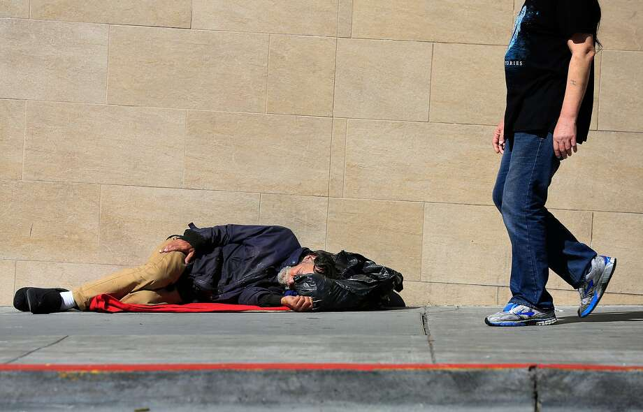 Pedestrians walk past a person lying on the sidewalk on Jones Street in San Francisco. Homelessness is among the greatest concerns of S.F. voters. Photo: Lea Suzuki / The Chronicle