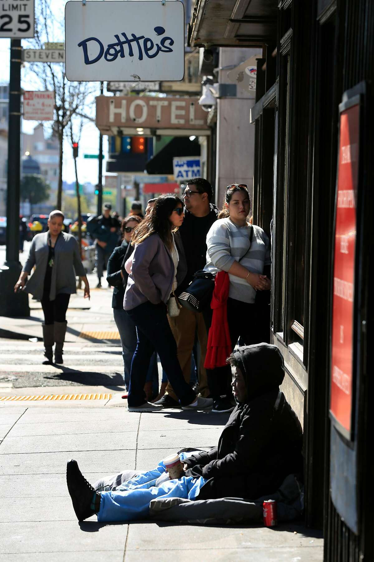 Aisha Matthews sits on the sidewalk next to a line of people waiting in line to enter Dottie's True Blue Cafe on 6th Street on Friday, April 13, 2018, in San Francisco, Calif. Matthews says she has been homeless for about 18 years.