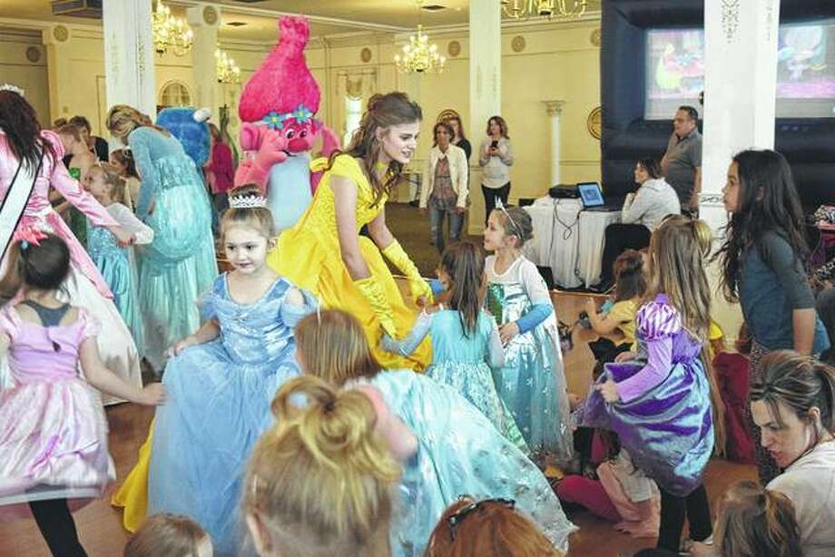 "Kaylee Ford of Franklin, dressed as Belle from ""Beauty and the Beast,"" invites some of the crowd to dance at the Princess Party Sunday at Hamilton's. Photo:       Audrey Clayton 