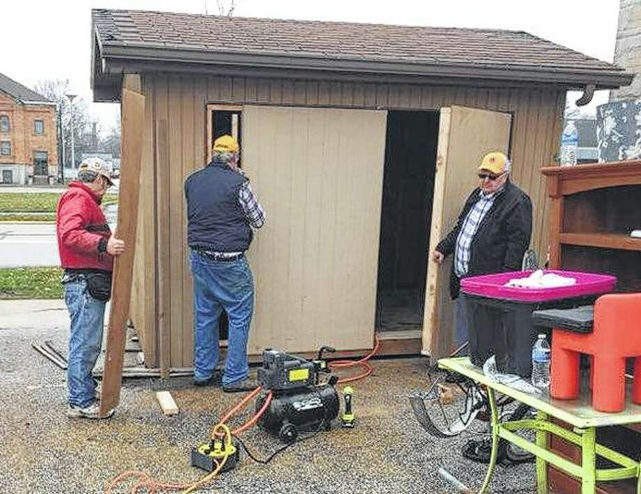 Lions Club members Ron Price, Tom Atkins and Larry Whewell work to replace the door on a storage shed at New Directions Warming and Cooling Center. Photo:       Photo Provided