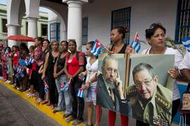 FILE - In this Dec. 3, 2016 file photo, women hold a portrait of the late Fidel Castro, and of his brother Cuba's President Raul Castro, as they wait to see the arrival of the caravan transporting Fidel's ashes from Havana, in Santiago, Cuba. The caravan was fraught with symbolism as the island nation buried the only leader it had known besides his younger brother, Raul, in 57 years. (AP Photo/Ricardo Mazalan, File)
