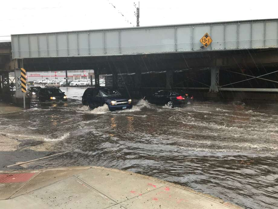 Cars and trucks fording the flooding waters under the Metro North bridge at East Main Street and Crystal Street on Monday morning. Photo: John Nickerson / Staff