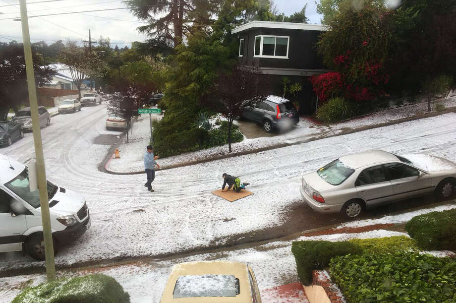 "A child turns a sheet of plywood into a ""sled"" to take advantage of a hill slippery with hail as strong shower produced a hailstorm in Oakland's Redwood Heights neighborhood on Monday morning, April 16, 2018. Photo: Twitter / @mediagrunt"