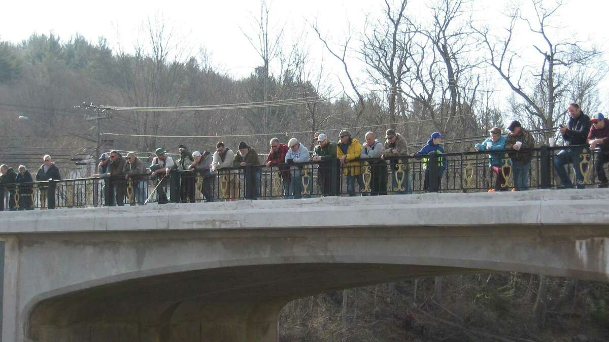 A crowd watches the fishing derby from the bridge above the Farmington River in Riverton on Saturday morning.