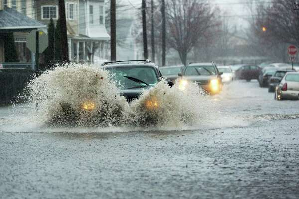A vehicle drives through deep water on a flooded Cottage Street in Bridgeport, Conn. on Monday, April 16, 2018. Excessive runoff from heavy rainfall caused flooding in many areas and resulted in a flash flood warning for Fairfield County.