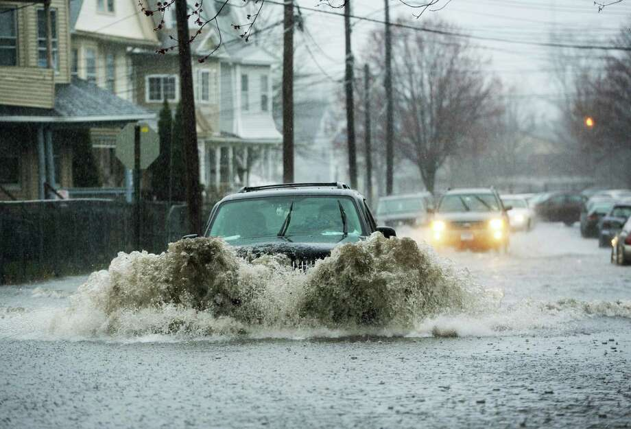 A vehicle drives through deep water on a flooded Cottage Street in Bridgeport, Conn. on Monday, April 16, 2018. Excessive runoff from heavy rainfall caused flooding in many areas and resulted in a flash flood warning for Fairfield County. Photo: Cathy Zuraw / Hearst Connecticut Media / Connecticut Post