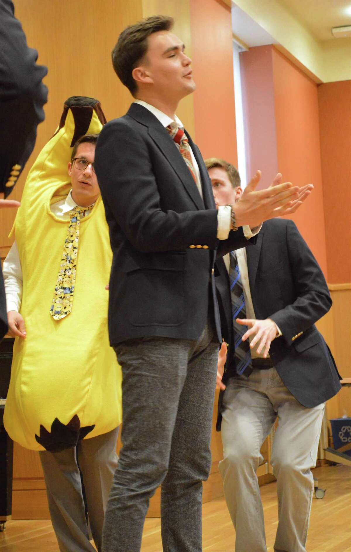 With Andres Pascual-Leone wearing the banana costume behind him, Markus Prostko solos at the performance of Amherst College's a cappella group The Zumbyes, at Darien Library, Sunday, April 15, 2018, in Darien, Conn.