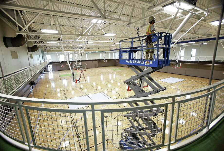 Goal suspension systems are checked as work wraps up on April 12 at Das Rec. The hardwood floor in the gym covers two full-size basketball courts and additional practice courts. Photo: Tom Reel /San Antonio Express-News / 2017 415916Z.1 ANTONIO EXPRESS-NEWS