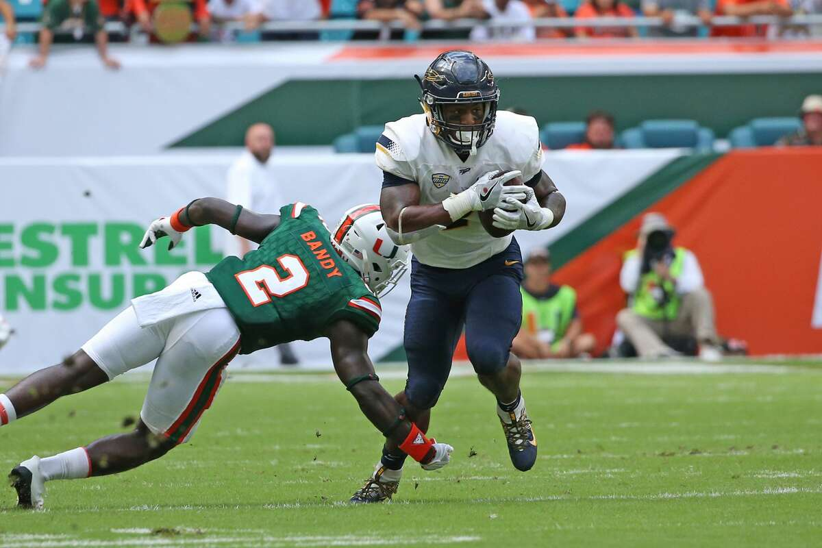 MIAMI GARDENS, FL - SEPTEMBER 23: Terry Swanson #2 of the Toledo Rockets runs with the ball past Trajan Bandy #2 of the Miami Hurricanes on September 23, 2017 at Hard Rock Stadium in Miami Gardens, Florida. (Photo by Joel Auerbach/Getty Images)