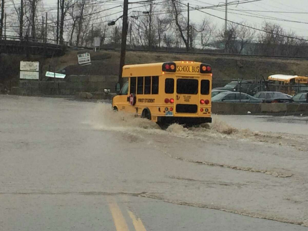 Vehicles venture through flooded roadway on Middletown Avenue in New Haven