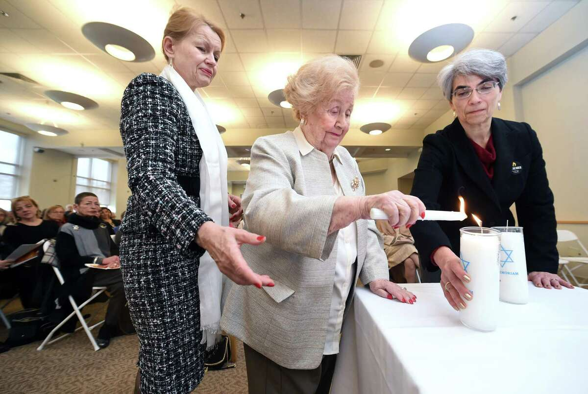 Holocaust survivor Shifra Zamkov, center, lights one of six candles representing 1 million of 6 million Jews killed in the Holocaust during the Yom HaShoah Community Observance with the help of Shaban Taisa, left, and Barbara Katz at Tower One/Tower East in New Haven Sunday.
