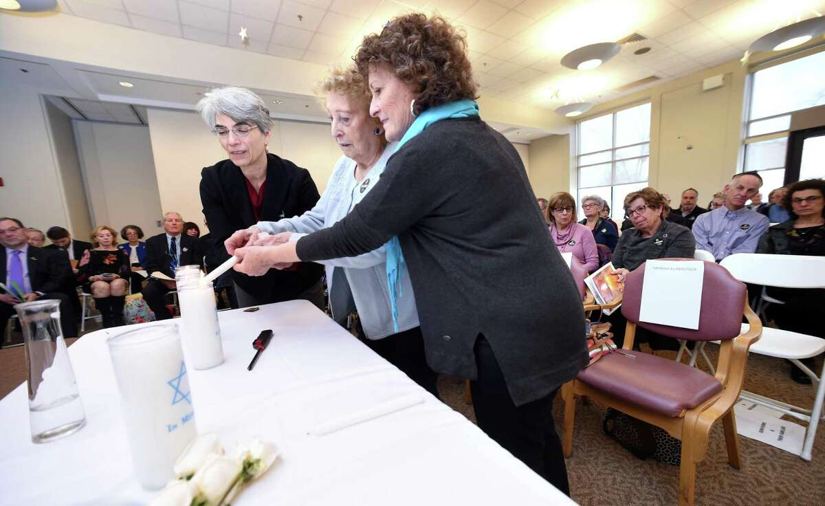 Holocaust survivor Hannah Kuperstoch, center, lights one of six candles during the observance with the help of her daughter, Mim Ramadei, right, and Barbara Katz.