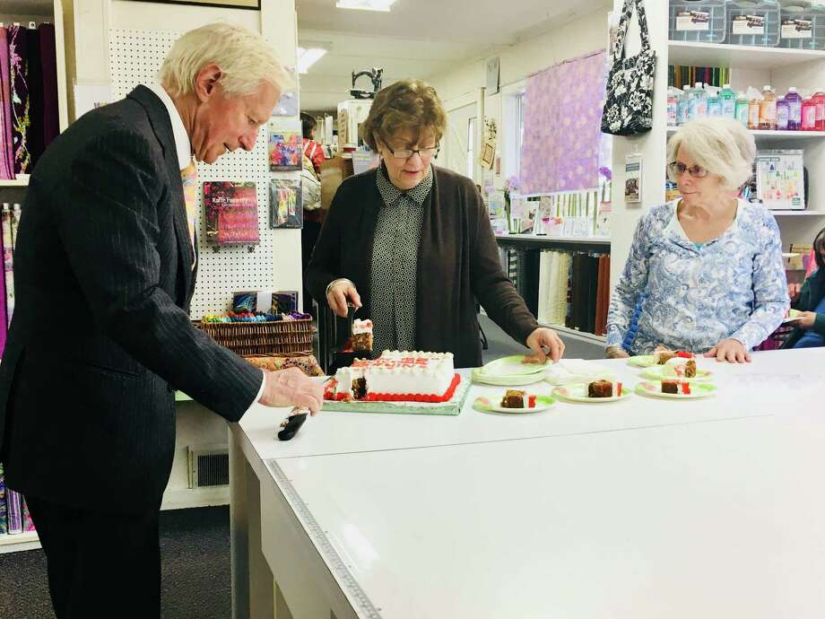 Hanspeter Ueltschi, chairman and owner of the Swiss sewing machine maker Bernina, cuts pieces of cake celebrating the company's 125th anniversary on Monday April 16, 2018 at the Gloversville Sewing Center. Ueltschi made the stop as part of a special anniversary celebration with the company's top dealers and its customers.