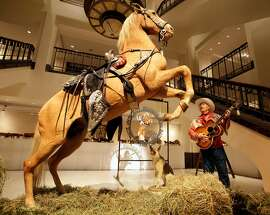 """Gil Perez, right, a doorman at Christies auction house, wears an outfit and holds a guitar belonging  to Roy Rogers as he stands alongside the preserved remains of Rogers' horse """"Trigger"""" and dog """"Bullet""""  at  the New York auction house,  Friday, July 9,2010.  Christie's held a preview Friday of an upcoming auction of items from the now-closed Roy Rogers and Dale Evans Museum in Branson, Mo."""