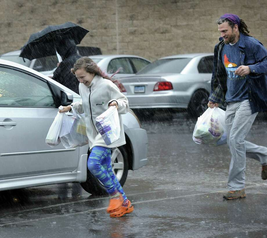 Lily Nyarady, 10, and her father, Michael, run to their car to escape from the pouring rain Monday morning at Stop and Shop on Mill Plain Road in Danbury. Lily is off from school for Spring break. Photo: Carol Kaliff / Hearst Connecticut Media / The News-Times