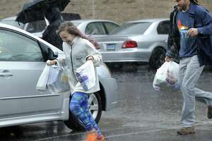 Lily Nyarady, 10, and her father, Michael, run to their car to escape from the pouring rain Monday morning at Stop and Shop on Mill Plain Road in Danbury. Lily is off from school for Spring break.
