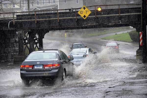 Cars splash through a flooded railroad underpass on West Street in Danbury during Monday's rain storm, April 16, 2018.