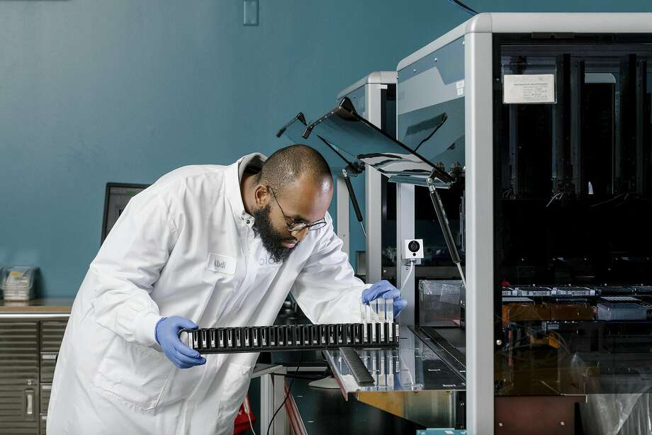 Abdi Khalif, who works in research and development, looks over samples at Color Genomics in Burlingame. Below: a customer's saliva sample at the lab, which many major companies work with. Photo: Photos By Jason Henry / New York Times