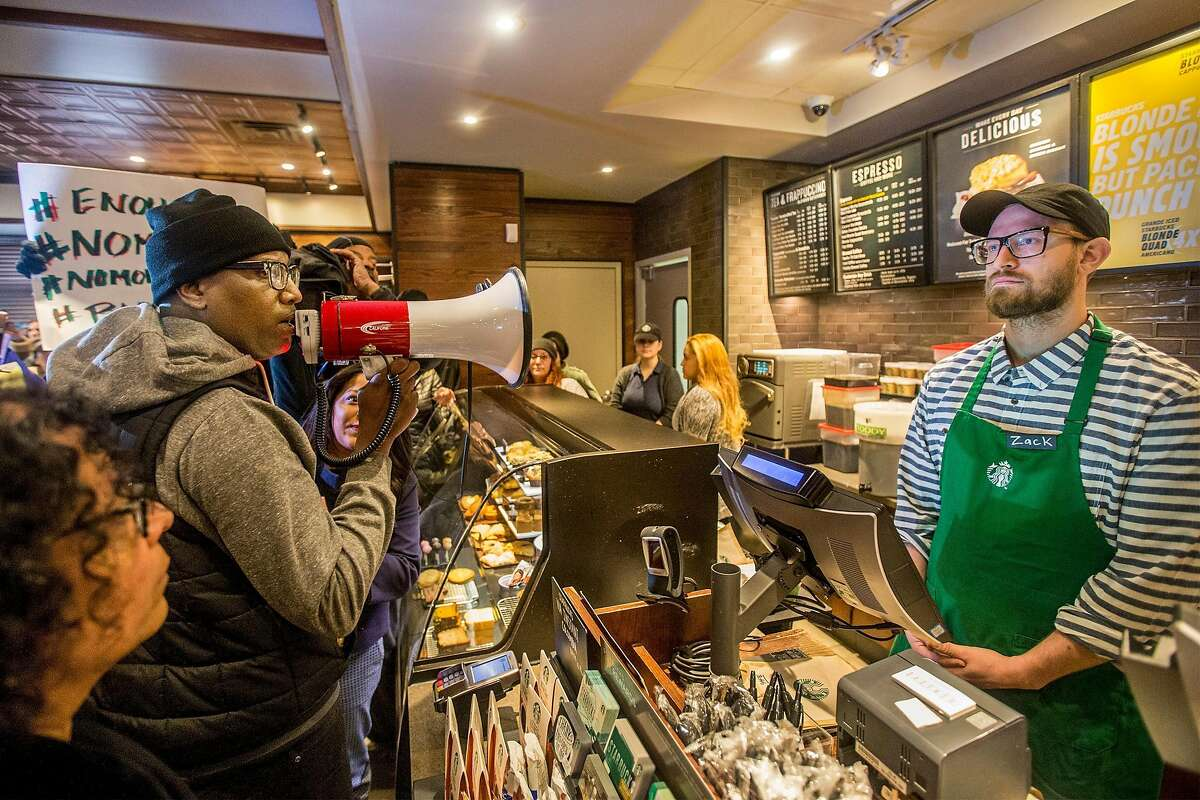 Local Black Lives Matter activist Asa Khalif, left, stands inside the Starbucks at 18th and Spruce, and over a bullhorn, demands the firing of the manager that called police, which resulted in two black men being arrested. On Sunday April 15, 2018, protesters demonstrated outside the Starbucks and planned to return Monday. (Michael Bryant//Philadelphia Inquirer/TNS)