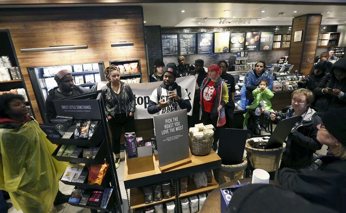 Demonstrators occupy the Starbucks that has become the center of protests Monday, April 16, 2018, in Philadelphia. The CEO of Starbucks arrived in Philadelphia hoping to meet with two black men who were arrested when the coffee chain's employees called 911 and said they were trespassing. Meanwhile, protesters took over the shop Monday. (AP Photo/Jacqueline Larma)