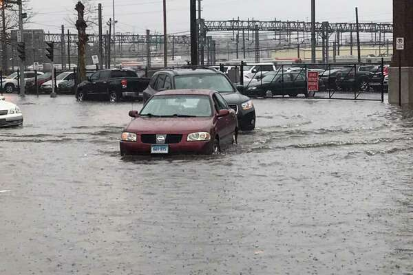 Cars wade through a mini river near the New Haven Police Department Monday.