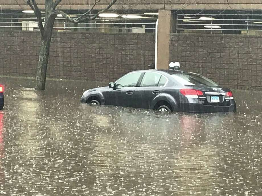 Cars wade through a mini river near the New Haven Police Department Monday. Photo: By Jessica Lerner
