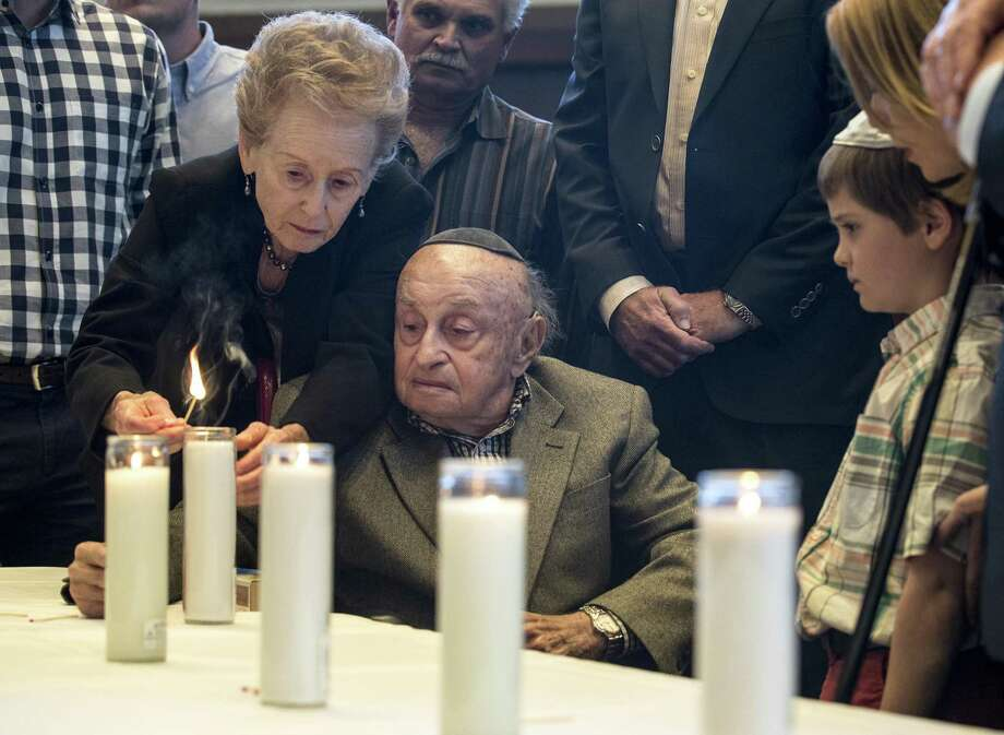 Ahuva Stopnicki helps her husband, Sol, light a candle during the Citywide Yom HaShoah Observance at Congregation Emanu El on Sunday, April 15, 2018, in Houston. Yom HaShoah is a day of remembrance of the 6 million Jewish people who lost their lives during the Holocaust. The ceremony also honors those who survived, coming together to remember and reflict., ( Brett Coomer / Houston Chronicle ) Photo: Brett Coomer, Staff / Houston Chronicle / © 2018 Houston Chronicle