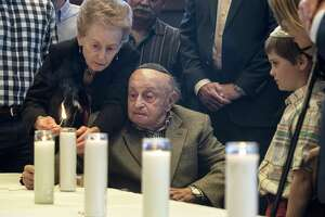 Ahuva Stopnicki helps her husband, Sol, light a candle during the Citywide Yom HaShoah Observance at Congregation Emanu El on Sunday, April 15, 2018, in Houston. Yom HaShoah is a day of remembrance of the 6 million Jewish people who lost their lives during the Holocaust. The ceremony also honors those who survived, coming together to remember and reflict., ( Brett Coomer / Houston Chronicle )