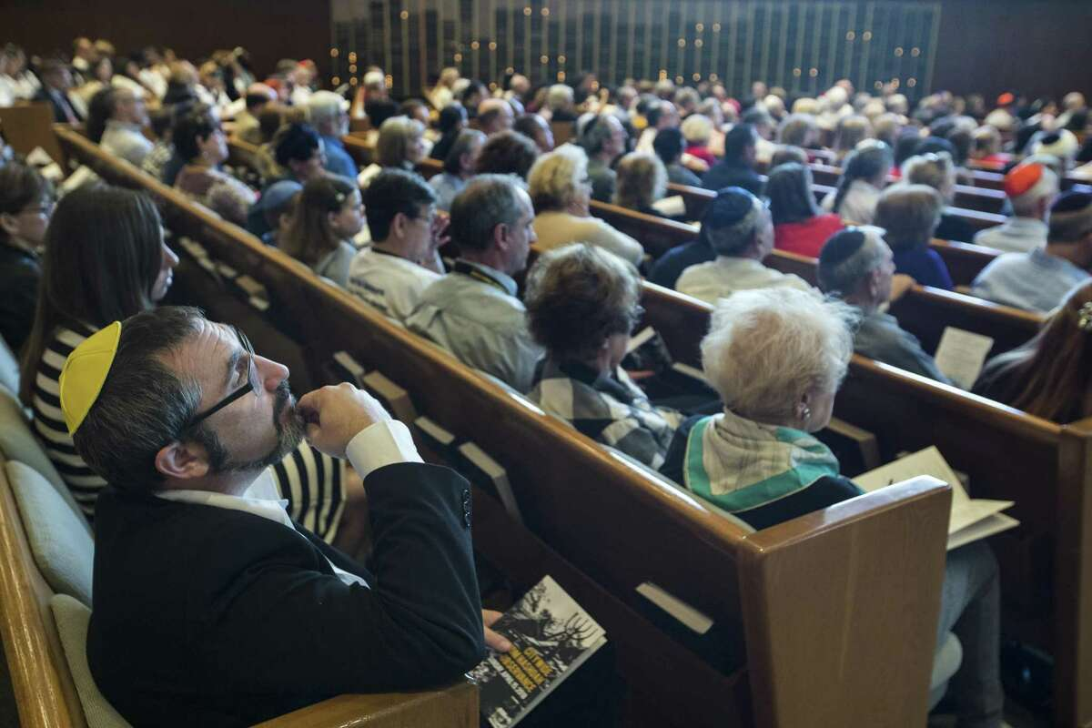 People listen to Gilad Katz, Consul General of Israel to the Southwest, speak during the Citywide Yom HaShoah Observance at Congregation Emanu El on Sunday, April 15, 2018, in Houston. Yom HaShoah is a day of remembrance of the 6 million Jewish people who lost their lives during the Holocaust. The ceremony also honors those who survived, coming together to remember and reflict., ( Brett Coomer / Houston Chronicle )