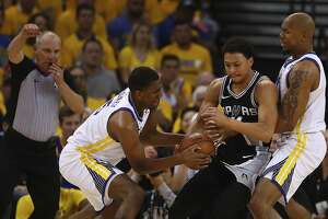 Golden State Warriors' Kevon Looney, left, steals the ball during the second half in Game 1 of a first-round NBA basketball playoff series against the San Antonio Spurs Saturday, April 14, 2018, in Oakland, Calif. (AP Photo/Ben Margot)