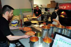 Waiter Jamie McGauran retrieves an order at Pizzaco, a new pizza restaurant along Stratford Avenue in Stratford, Conn., on Tuesday Mar. 28, 2017. The building was converted from a car repair shop and before that a gas station and kept that theme inside and out. Stratford's Restaurant Week begins Sunday, April 22, 2018.