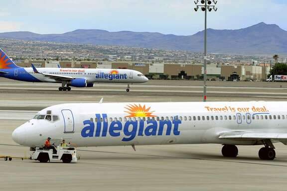 """File - In this May 9, 2013, file photo, two Allegiant Air jets taxi at McCarran International Airport in Las Vegas. Shares of Allegiant Air's parent company are tumbling in Monday, April 16, 2018, premarket trading following a """"60 Minutes"""" investigation that expressed serious safety concerns about the airline. (AP Photo/David Becker, File)"""
