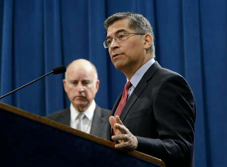 FILE - In this Wednesday, March 7, 2018 file photo, California Attorney General Xavier Becerra, right, accompanied by Gov. Jerry Brown, right, discusses remarks made by U.S. Attorney General Jeff Sessions, in Sacramento, Calif. Becerra, a Democrat, filed a federal lawsuit immediately after U.S. Commerce Secretary Wilbur Ross announced a citizenship question would be added to the 2020 census. The nation's most populous state also has the highest number of foreign-born residents, most of whom are naturalized U.S. citizens or hold some other legal status. (AP Photo/Rich Pedroncelli)